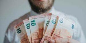 persona che mostra un ventaglio di banconote da 100 euro